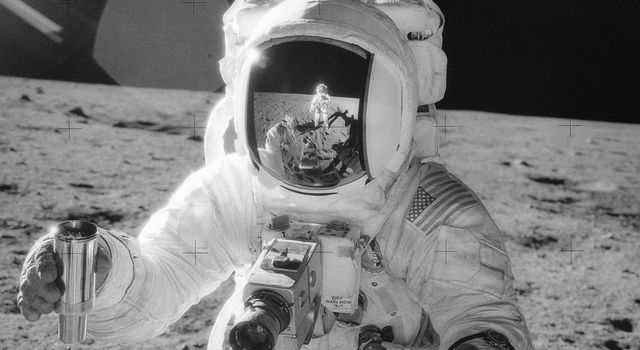 Apollo 12 lunar module pilot Alan Bean holds a container of lunar soil