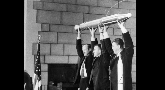 A model of Explorer 1, held by JPL's Director William Pickering, scientist James Van Allen and rocket pioneer Wernher von Braun