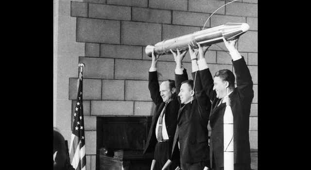 A model of Explorer 1 is held high