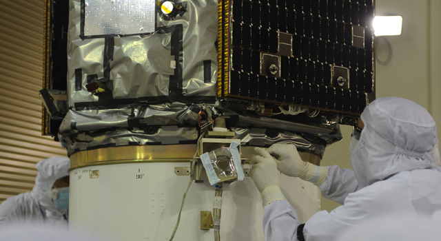 Readying NASA's Orbiting Carbon Observatory-2 for launch, a technician attaches the observatory to the payload attach system in a clean room at Vandenberg Air Force Base in California