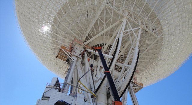 Workers at NASA's Deep Space Network complex in Goldstone, Calif., use a crane to lift a runner segment that is part of major surgery on a giant, 70-meter-wide antenna.