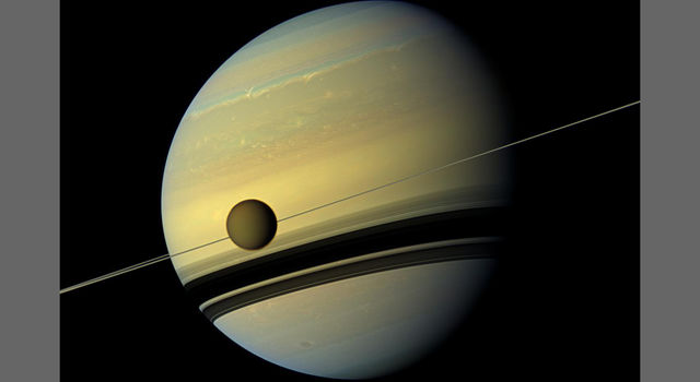 Huge moon Titan is seen here as it orbits Saturn