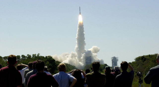 At 11:02 a.m. EDT on April 7, 2001, crowds watch a Boeing Delta II rocket lift off from Cape Canaveral