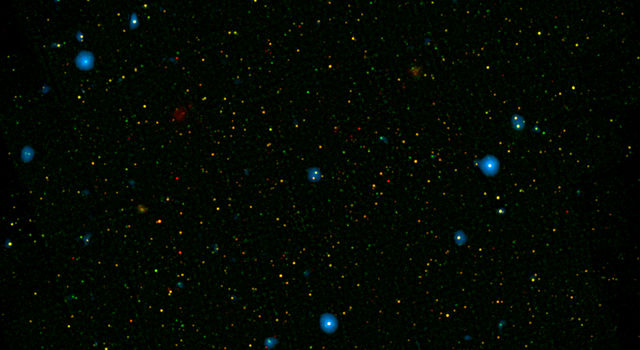 The blue dots in this field of galaxies, show galaxies that contain supermassive black holes emitting high-energy X-rays.