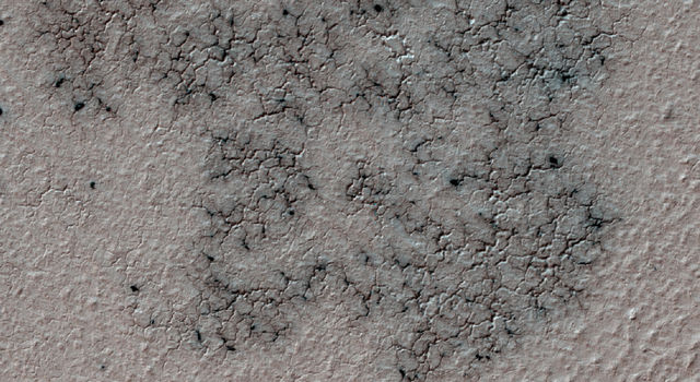 This image shows spidery channels eroded into Martian ground.