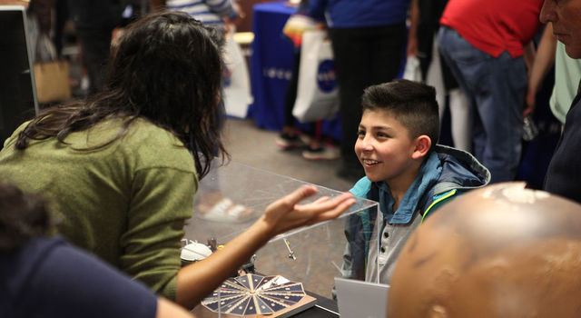 Amruta Mehta, a member of the Mars InSight Roadshow, speaks with a boy at one of the Roadshow's stops in Santa Maria