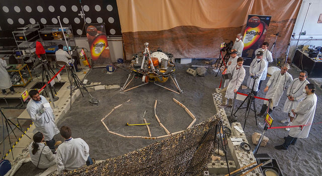 Engineers sculpt a gravel-like material to mimic the terrain in front of NASA's InSight lander on Mars.