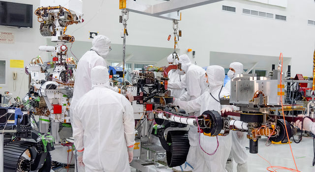 On June 21, 2019, engineers at NASA's Jet Propulsion Laboratory install the main robotic arm on the Mars 2020 rover