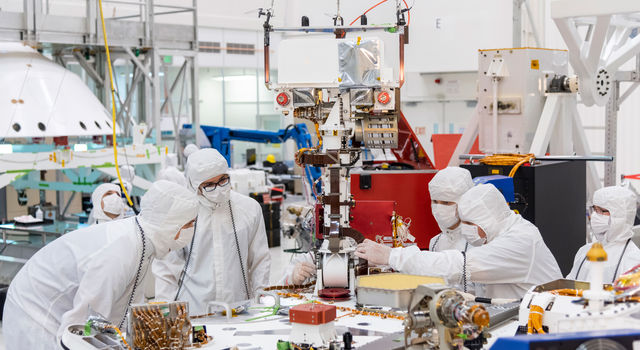 Engineers and technicians at NASA's Jet Propulsion Laboratory in Pasadena, California, install the remote sensing mast on the Mars 2020 rover