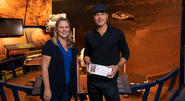 "The actor Brad Pitt (right) shows off his ""boarding pass"" for Mars with Jennifer Trosper (left), the Mars 2020 project systems engineer"