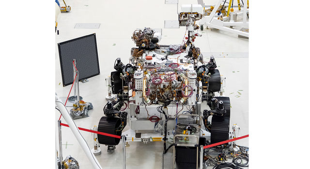 Engineers in clean room circling Mars 2020 rover as it undergoes an