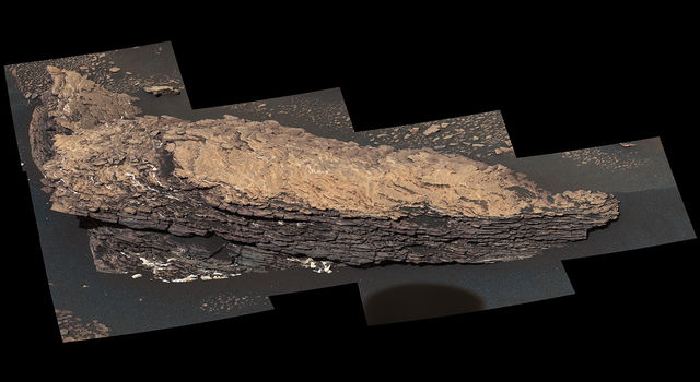 Mast camera mosaic of images shows layers of sediment on a boulder-sized rock called Strathdon