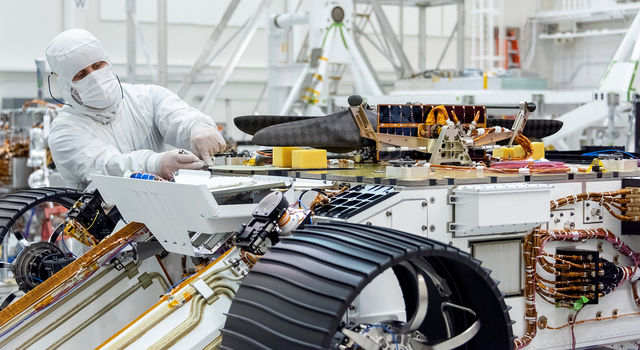 An engineer works on attaching NASA's Mars Helicopter to the belly of the Mars 2020 rover