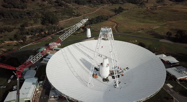 A 400-ton crane lifts the new X-band cone into the 70-meter (230-feet) Deep Space Station 43 dish