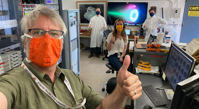 Thumbs-up for a successful test. Psyche engineers observe COVID-19 social-distancing and masking requirements as they test an electric Hall thruster
