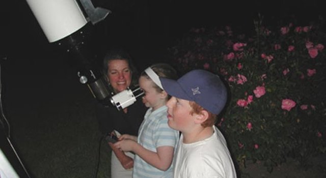 Little girl looks through a telescope; little boy waits his turn to view Saturn