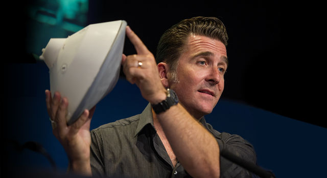 Adam Steltzner of JPL holds up a model of a Mars entry capsule.