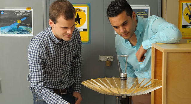 RainCube's radiofrequency lead Nacer Chahat (right) and mechanical engineer lead Jonathan Sauder (left) observe the CubeSat's deployed antenna.