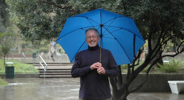 Dr. Bill Patzert stands under an umbrella