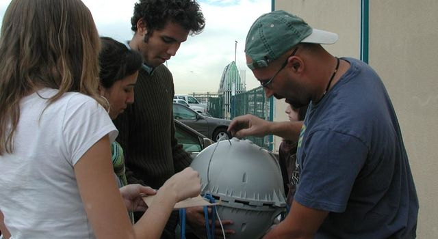 team prepares to attach data cable to buoy