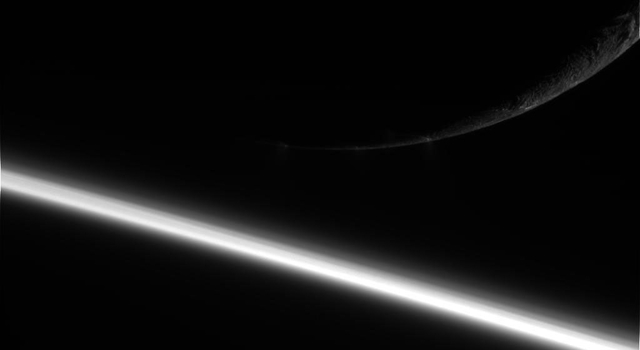 This image, taken on August 13, 2010, by NASA's Cassini spacecraft, shows the moon Enceladus over the bright arc of Saturn's atmosphere.