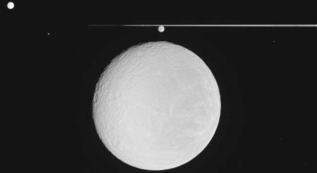 NASA's Cassini spacecraft captured this raw image of Saturn's icy moon Rhea in the foreground