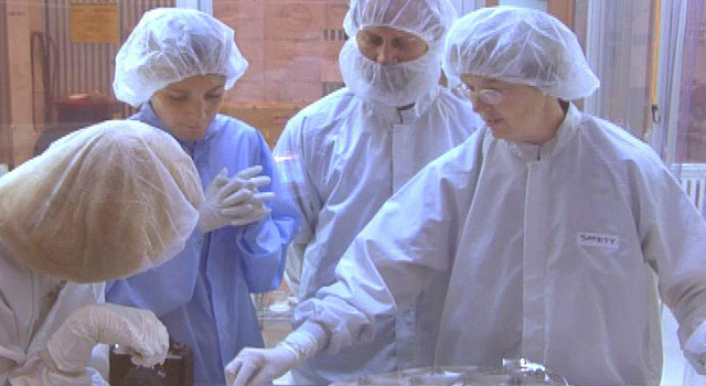 Genesis cleanroom team members looks at recovered samples