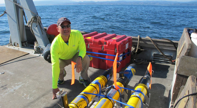 JPL's Steve Chien with several of the underwater drones