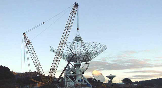 The dish is lifted into position on the new antenna being built near Madrid.