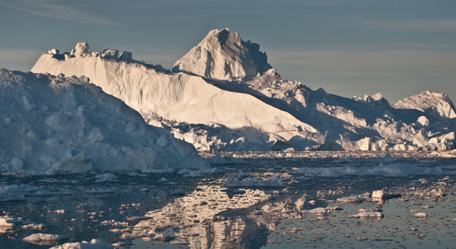 The midnight sun casts a golden glow on an iceberg and its reflection in Disko Bay