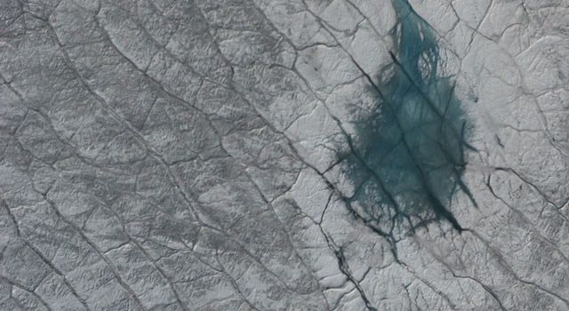 A grayish turquoise melt pond on the Greenland ice sheet, as seen from the air. Credit: NASA