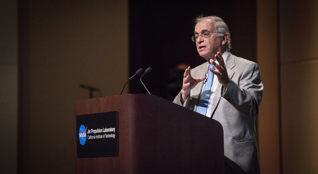 Charles Elachi speaks behind a podium in Pickering Auditorium at JPL.