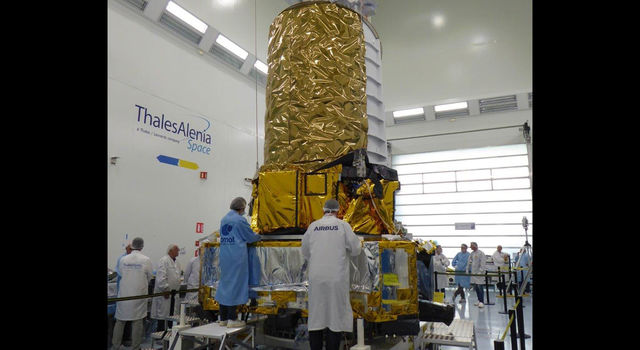Technicians with the manufacturer Thales Alenia Space work with the structural and thermal model