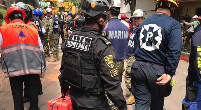 An emergency responder in Mexico City carries an orange case holding a radar instrument called FINDER.