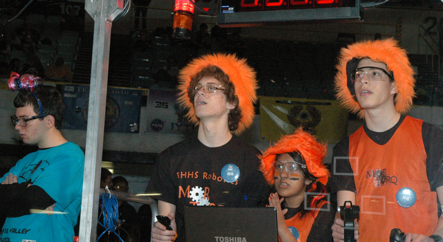 A team sporting orange, fuzzy hats is seen here controlling their robot in the midst of a match.