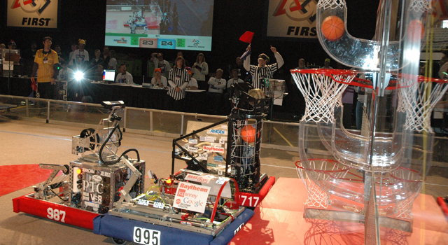 Student-controlled robots compete at the FIRST Robotics Competition by shooting foam basketballs into hoops.