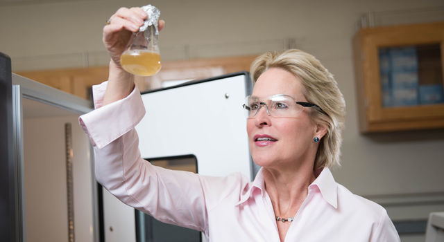 Frances Arnold examines a beaker in the Lab at Caltech.
