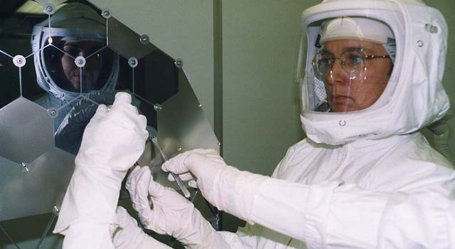 Dr. Eileen Stansbery, JSC cleanroom designer, assembles one of Genesis'delicate solar arrays in NASA's cleanest room