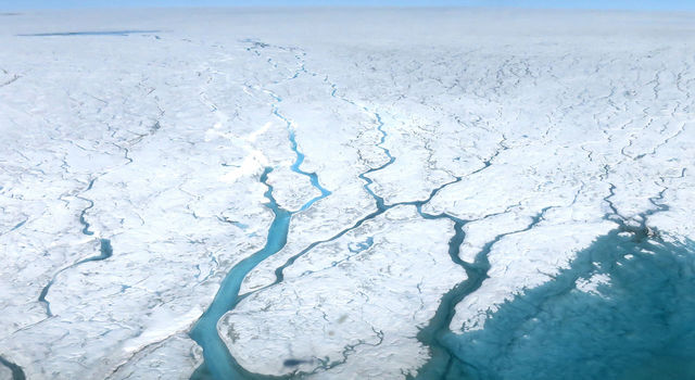 This aerial photograph shows fast-moving meltwater rivers flowing across the Greenland Ice Sheet