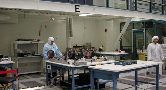 A Mars Exploration Rover project engineer works on the wheels of one of the twin rovers to be launched in 2003