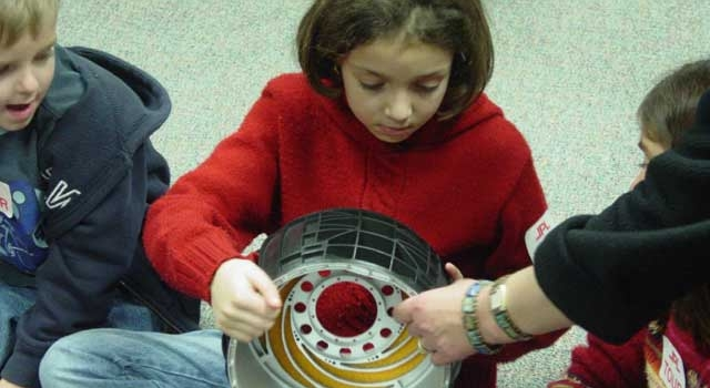 A student examines a model wheel for the rover.