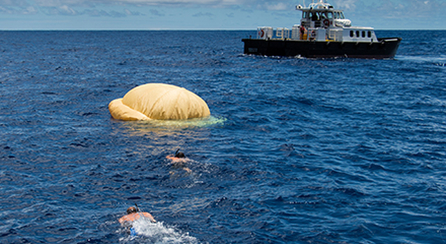 Two members of the Navy's Explosive Ordinance Disposal swim towards the LDSD test vehice. In the background, the recovery vessel Mana'o II.