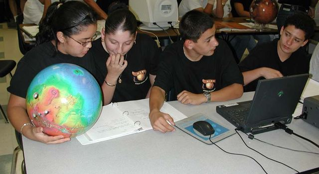 Students study globe of Mars