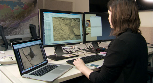 Scientist Katie Stack Morgan examines rover images on her computer.