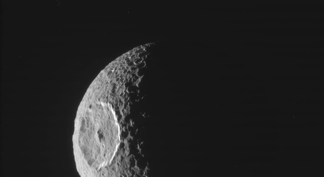 NASA's Cassini spacecraft obtained this raw image of the moon Mimas on Oct. 16, 2010, just before Mimas went into shadow behind Saturn.