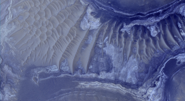 Layers in the lower portion of two neighboring buttes within the Noctis Labyrinthus formation on Mars are visible in this image from the High Resolution Imaging Science Experiment camera on NASA's Mars Reconnaissance Orbiter.