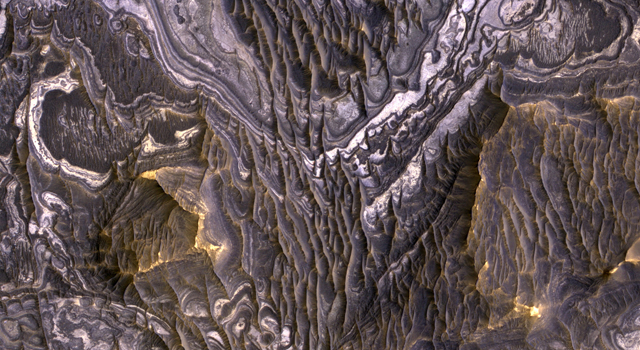 This view shows color variations in bright layered deposits on a plateau near Juventae Chasma in the Valles Marineris region of Mars.