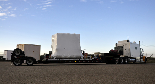 NASA's NuSTAR spacecraft, enclosed in an environmentally controlled shipping container, is delivered by tractor-trailer to processing facility 1555 at Vandenberg Air Force Base in California.