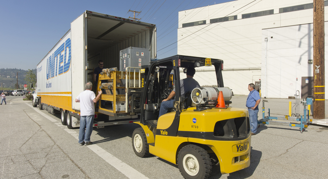 Technicians load the OCO-2 instrument and its ground support equipment aboard a moving van at JPL