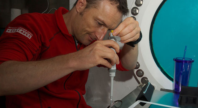 Matthias Maurer of ESA inserts samples into the MinION DNA sequencer